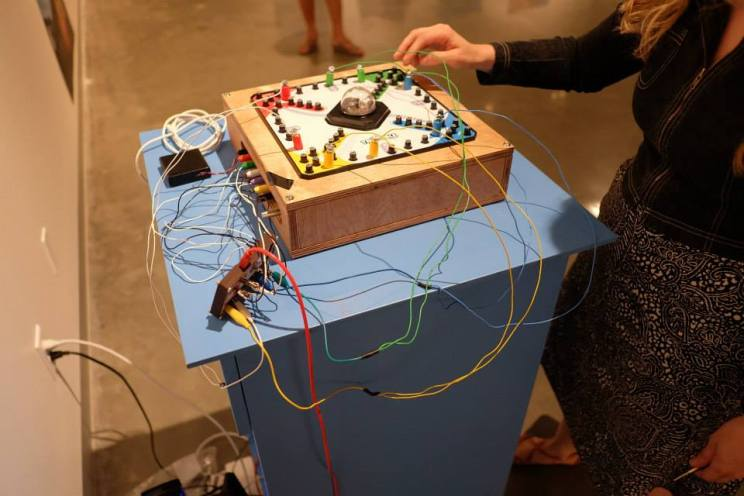 "The Trouble Board, a board game prepared with metal contact points for each space along the game path and an embedded microphone under the ""pop-o-matic"" bubble dice—allow audience members to control a digital soundscape through play. A Makey-Makey microprocessor circuit and a custom-made software patch allow movement around the board and the clicking of the bubble dice to trigger the playback of sound files and process the sound of the dice roll in real-time."