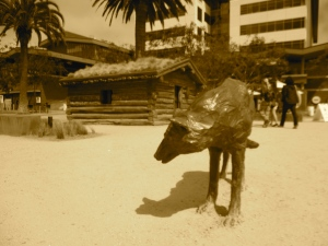 A statue of a wolf in Jack London Square. In the background, part of the cabin London lived in while mining gold in the Yukon.